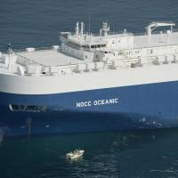 Search for evidence: A Japan Coast Guard boat approaches the Norwegian car carrier NOCC Oceanic off Sendai on Tuesday morning to determine whether it was involved in a collision Sunday with a tuna trawler, whose skipper remains missing. | KYODO