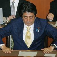 'Tis but a scratch: Prime Minister Shinzo Abe bows as the Upper House passes a censure motion Wednesday. | KYODO