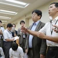 Official OK: Health Ministry officials answer questions from reporters Wednesday in Tokyo after the ministry's panel gave the green light to kick off clinical research using iPS cells for retinal regeneration. | KYODO