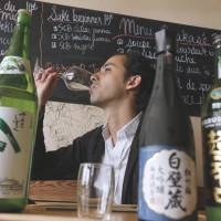 Drink up!: Sake Bar manager Youlin Ly tastes a glass of Japanese sake in Paris on June 18. | AFP-JIJI