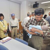 You're never too old to learn: A baby boomer uses a doll to learn how to hold a baby in a program to help older men learn the basics of nurturing babies. | KYODO