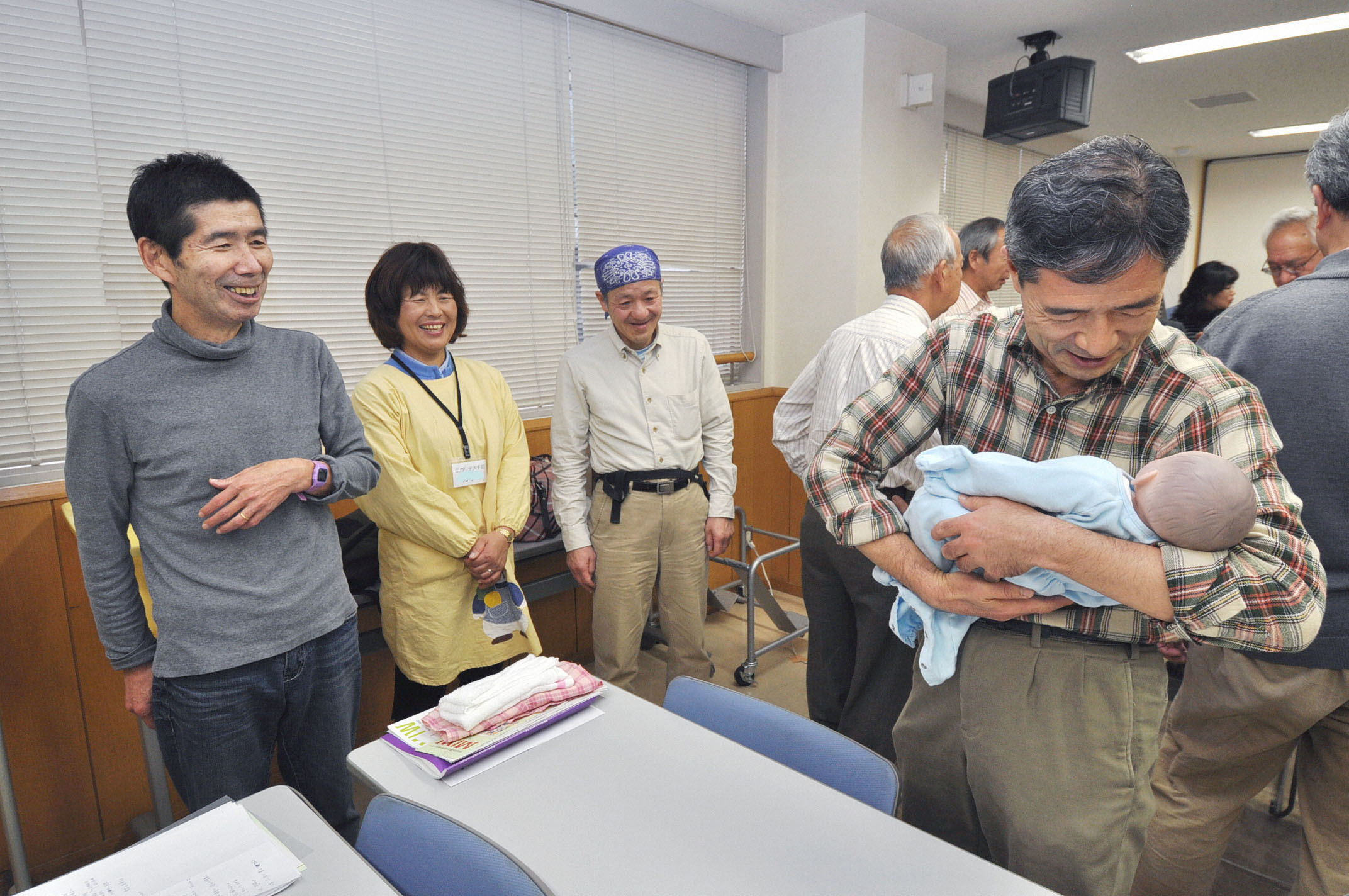 You're never too old to learn: A baby boomer uses a doll to learn how to hold a baby in a program to help older men learn the basics of nurturing babies.   KYODO