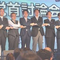 Center stage: Prime Minister Shinzo Abe (fourth from left) and New Komeito chief Natsuo Yamaguchi (third from right) of the ruling coalition join hands with opposition leaders following a debate in Tokyo on Friday. | AFP-JIJI