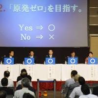 Going it alone: Liberal Democratic Party Secretary-General Shigeru Ishiba displays an X sign to show he is opposed to phasing out nuclear power, at a policy debate Saturday in Osaka involving all nine major political parties. The LDP was the only one opposed. | KYODO