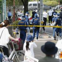 Crime scene: Passersby watch as police comb the scene where a man stabbed three elementary school boys Friday in Nerima Ward, Tokyo.  | KYODO
