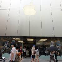 Taking a bite: Pedestrians walk past an Apple Inc. store in Tokyo's Ginza district Sunday.  | BLOOMBERG