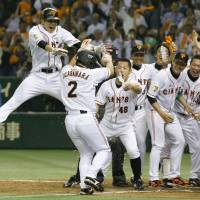 Come on home: The Giants meet Michihiro Ogasawara (2) at home plate after his sayonara home run against the Fighters on Wednesday at Tokyo Dome. | KYODO