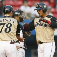Good start: Hokkaido Nippon Ham's Sho Nakata (right) is welcomed home after hitting a two-run home run in the first inning of the Fighters' 5-3 win over the Marines on Monday. | KYODO