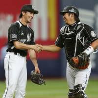 So close: Lotte's Takuya Furuya is congratulated by catcher Tomoya Satozaki after his one-hit shutout on Wednesday. | KYODO