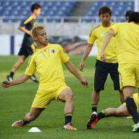 Finishing touches: Keisuke Honda (left) kicks the ball during a Japan training session on Monday. | KYODO