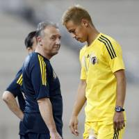 Sit this one out: Japan forward Keisuke Honda walks across the training field with ice strapped to his leg in Doha on Sunday. | KYODO