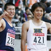 Budding rivalry: Yoshihide Kiryu (left) and Ryota Yamagata pose for pictures after the 100-meter race at the National Championships at Tokyo's Ajinomoto Stadium on Sunday. | KYODO