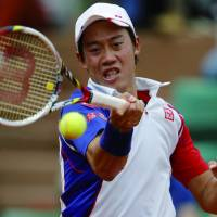 On the brink: Kei Nishikori hits a return against Benoit Paire during the third round of the French Open. Nishikori won the match 6-3, 6-7 (3-7), 6-4, 6-1 to reach the fourth round. | KYODO