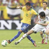 Hard to handle: Neymar (left) takes the ball away from Japan captain Makoto Hasebe during Brazil's 3-0 win on Saturday.   AP