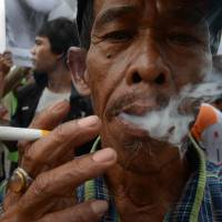 Smoking 'em out: A man takes part in a counterprotest to denounce  World No Tobacco Day in Jakarta on Friday. | AFP-JIJI