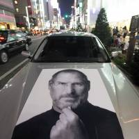 Omnipresent: An image of Steve Jobs, Apple's late CEO, decorates a car outside the Apple store in Ginza in September. | BLOOMBERG