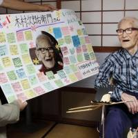Good innings: Jiroemon Kimura, the world's oldest person, receives messages written by students of a local elementary school in Kyotango, Kyoto Prefecture, last Sept. 17. Kimura died Wednesday at the age of 116.  | KYOTANGO MUNICIPAL GOVERNMENT/KYODO