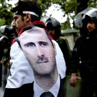 A Syrian man wrapped in a national flag with a portrait of President Bashar Assad walks past riot police during an anti-Israel demonstration in Tehran on May 6. | AP