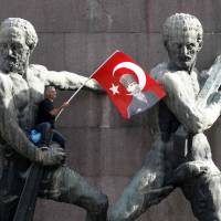 Waving the red flag: A demonstrator waves Turkey's national flag after climbing onto a monument in Ankara on Sunday during a protest against Prime Minister Recep Tayyip Erdogan and his ruling Justice and Development Party. | REUTERS/KYODO