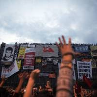 Enraged: Protesters shout slogans in front of the Ataturk Cultural Center during a rally Tuesday in Istanbul's Taksim Square. | AP