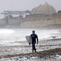Surf and turfed: A surfer walks along the shore at San Onofre State Beach early Friday morning as the San Onofre nuclear plant looms in the background. | AP