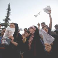 Young at heart: Supporters of Iranian presidential candidate Hasan Rowhani hold campaign posters during a street rally at Vanak Square in Tehran on Wednesday. | AFP-JIJI