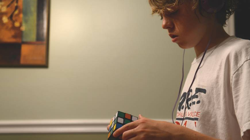 James Barden, 13, listens to music while working on a Rubick's Cube at home. | THE WASHINGTON POST