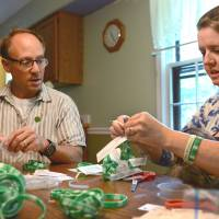 Mark and Jackie Barden package rubber bracelets in memory of their slain son. | THE WASHINGTON POST
