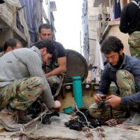 Bigger things on the way: Members of the rebel Free Syrian Army prepare their weapons in the Aleppo neighborhood of al-Amerieh in April. | AP