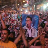 Who's your Palestinian?: Palestinians in the West Bank city of Ramallah celebrate early Sunday after Mohammed Assaf won on the 'Arab Idol' show. | AFP-JIJI