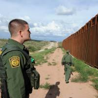 Line of control: U.S. Border Patrol agents examine the border between Arizona and Mexico near Nogales in July 2010. | AFP-JIJI