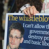 Wanted: A protester holds a placard during a rally in support of Edward Snowden, a former National Security Agency contractor, in Hong Kong on June 15. Snowden is being sought by the U.S. for alleged theft and breaches of the Espionage Act. | BLOOMBERG