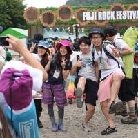 Visitors to this year's Fuji Rock Festival, which kicks off today and runs till July 28, pose for commemorative photos at the fest entranceway, which covers much of the Naeba ski resort.  | JAMES HADFIELD PHOTO
