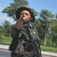 Pointed response: A Chinese soldier gestures at a checkpoint on the road to the riot-hit Uighur town of Lukqun on Friday, a week before the anniversary of major ethnic clashes in 2009. | AFP-JIJI