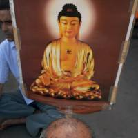 Against violence: A Buddhist protests in Kolkata on Sunday following a series of blasts at the Bodh Gaya complex in India's Bihar state. | AFP-JIJI