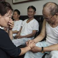 Second lives: Kim Kyung-hee, 40, bursts into tears as she speaks with Lee Sun-woo, 82, on Wednesday in Seoul. Lee was captured by Chinese troops during the Korean War in July 1953, 13 days before the armistice was signed, and detained as a prisoner to work in a coal mine until he escaped from North Korea in 2006. Kim escaped from North Korea in 2012; her late father, Kim Woo-yong, worked in the same coal mine as Lee from 1953 to 2004. | THE WASHINGTON POST