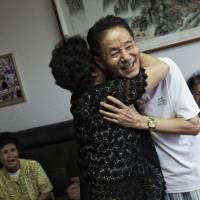 Emotional time: Park Hyang-sook (left), who escaped from North Korea in 2006 with the remains of her late husband, a prisoner of war from South Korea, embraces Lee Gyu-il, 80, a POW who escaped the North in 2008. | THE WASHINGTON POST