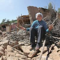 World of upset: A woman sits crying atop her collapsed house in Dingxi, Gansu province, on Tuesday. | AFP-JIJI