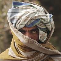 Eyes of the enemy?: A former Taliban fighter looks on after joining government forces during a ceremony in Afghanistan's Herat province in March 2012. | AFP-JIJI