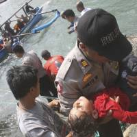 Rescued: An unconscious child is carried away after a boat filled with asylum seekers sank Wednesday off Java, Indonesia. | AP