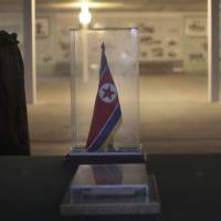 Us and them: A North Korean soldier walks past a display of the armistice agreement between the two Koreas at the truce village of Panmunjom in the demilitarized zone on Monday. | AP