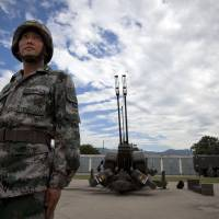 On alert: A People's Liberation Army soldier is seen at a base in Xian on Monday. In recent months Beijing has sent frigates and surveillance vessels to the disputed Spratly Islands in the South China Sea, setting off alarm bells in Manila. | AP