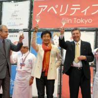 A lot of bottle: Junichi Ishida (center) shills for Aperitif Day as a 'goodwill ambassador' with Christophe Penot, deputy head of mission to the French Embassy in Japan, and Jean-Charles Crouin of French government wine promoter Sopexa Japon at Roppongi Hills in Tokyo in June. | YOSHIAKI MIURA PHOTO