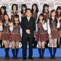 Angels with dirty faces: Veteran pop Svengali Yasushi Akimoto, center, stands with members from AKB48, one of the groups he has helped manufacture. AKB48's image of passive sexuality draws an obsessive audience, though it appeared to backfire last week when a man allegedly 'molested' female fans at one of their concerts. | KYODO PHOTO