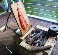 Slow food: A side of the salmon pinned to a cedar board with oak pegs cooks before a charcoal fire with some hardwood added to impart a nice smoky flavor. During the cooking, I kept dousing the fish with butter to enhance its succulence.