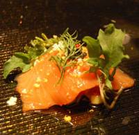 No fire: Spring Mist, a slice of salmon served with diced red peppers, zucchini and chestnuts, comes encased in a glass dome that traps a puff of smoke. | MELINDA JOE PHOTO