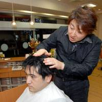 From top: Hideki Sato transforms a regular guy into a flat-top eye-catcher by wetting his hair; shaving his forehead hairline to create a straight edge; then drying and spraying his crowning glory to perfect a square-looking combed-back style — sometimes with the help of special tools such as this wire grid that makes the hair lie very flat. | YOSHIAKI MIURA PHOTOS