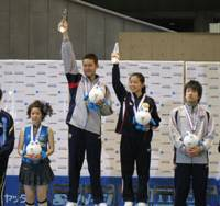 Naomi Yotsumoto (second from left, top) in her 'revolutionary' garb on the mixed-doubles podium after playing in last month's Table Tennis National Championships (above) held at the Tokyo Metropolitan Gymnasium (below). | EDAN CORKILL PHOTOS