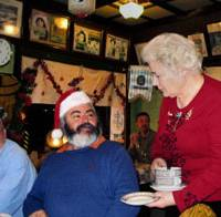 Festive: Frau Reiff serves a patron at the Sea Castle German restaurant's annual Christmas dinner. | COURTESY OF REIFF FAMILY