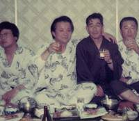Firm friends: Sitting beside his elder brother, Miyazaki (left) hosts a party for members of his company's staff at a Wakayama hotel in the late 1970s. | MANABU MIYAZAKI
